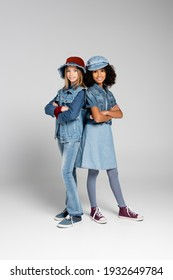 stylish interracial girls in denim clothes and gumshoes standing with crossed arms on grey
