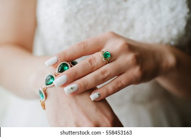 Stylish jewelry with gems of green. On the hands of women beautiful jewelry
