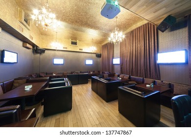 Stylish karaoke bar with leather armchairs and screens.