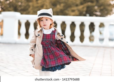 Stylish kid girl 1-2 year old wearing dress and jacket over city background closeup. Looking at camera. Childhood. French style.