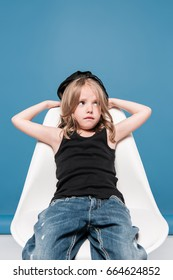 stylish kid girl looking away while sitting on chair