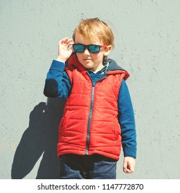 Stylish kid in trendy sunglasses. Kids fashion. Cute little blondy boy in red jacket standing over the grey wall outdoors in sunny day. Autumn, spring kids fashion. Kids sunglasses. Hipster style.