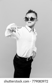 Stylish kid in white shirt and black pants wearing sunglasses posing in studio on gray background.