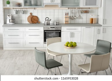 Stylish kitchen interior with dining table and chairs