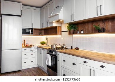 Stylish kitchen interior with modern cabinets and stainless steel appliances in new home. design in scandinavian style. cooking food. green plants decor, wooden worktop, sink and stove
