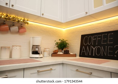 Stylish kitchen interior with modern coffeemaker on countertop
