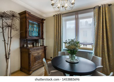 Stylish kitchen interior with nice furniture. Kitchen chest and round breakfast table with flowers