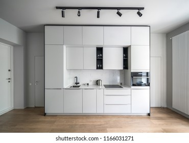 Stylish kitchen in a modern style with light walls and a parquet on the floor. There are white lockers and drawers, sink, stove, kettle, oven, shelves with glasses, black lamps, doors, long radiator.
