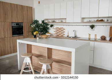 Stylish kitchen in white and brown wood. Style minimalism. Sink, table top, plants, pot, shelf for dishes. Bar stools, table.