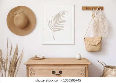 Stylish korean interior of living room with brown mock up poster frame, elegant accessories, flowers, wooden shelf and hanging rattan bags and hat. Minimalistic concept of home decor. Template.