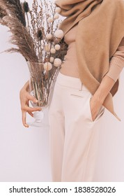 Stylish Lady in beige outfit with flowers decor.  Details of everyday look. Trendy minimalistic style. Beige aesthetics. Fashion look book. Warm Fall Winter seasons concept