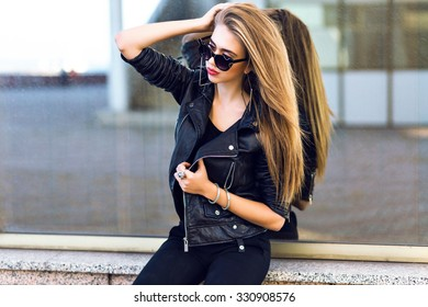 Stylish lady in black posing near mirrored wall, outdoor urban city portrait, glamour blonde model posing at cold autumn rainy day, stylish brutal leather black jacket, sunglasses, makeup.