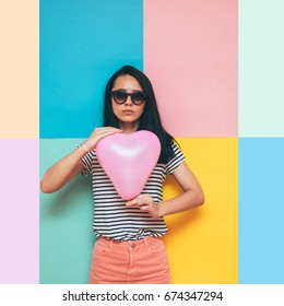 stylish lady holding a pink balloon in the shape of a heart