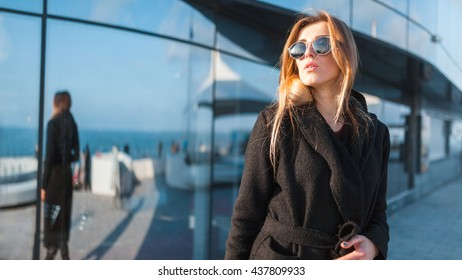 Stylish lady is posing in-front modern  building with plate-glass windows. She is wearing black coat and stylish sunglasses. There is her reflexion on the window