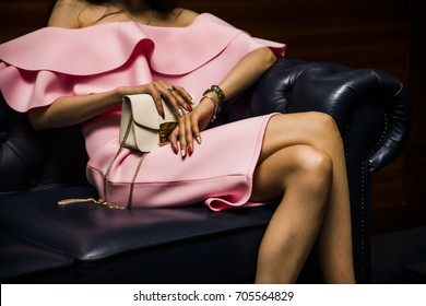 stylish lady woman posing on leather sofa wearing a pink purple dress and holding a white purse, handbag. no face, unrecognizable person. luxury young adult girl expensive accessories