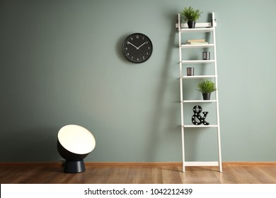 Stylish lamp with shelving unit near color wall