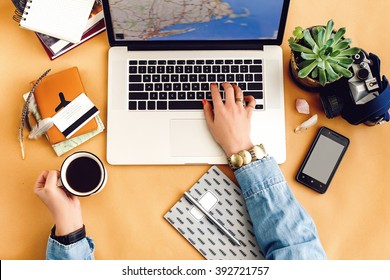 stylish laptop pen phone and succulent on craft background girl hands holding coffee, work and planning travel concept, flat lay