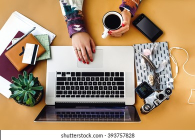 stylish laptop pen phone and succulent on craft background girl hands holding coffee,  planning vacation and freelance concept, flat lay