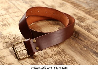 Stylish leather belt on wooden background