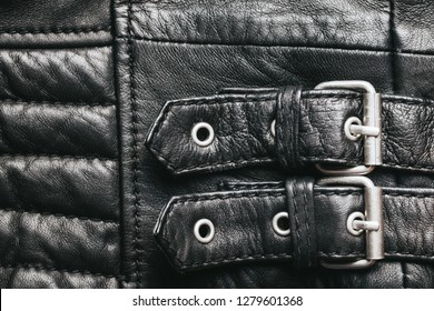 Stylish leather jacket with metal details and regulation strap.