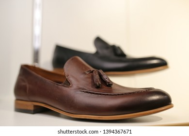 Stylish leather / lacquered men's shoes on the shelf in the store. Black / brown men's shoes on the stand. Male style, fashion.Men's shoes of black / brown leather on the she