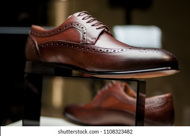 Stylish leather men's shoes and sneakers on the shelf in the store. Black / brown men's shoes on the stand. Male style, fashion. Gathering the groom. men's and women's shoes and sneakers. sneakers