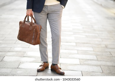 stylish leather suitcase carred by elegant men in brown shues