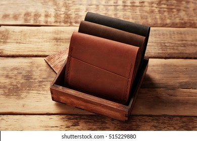 Stylish leather wallets in box on wooden background