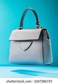 Stylish leather women's handbag on a blue background