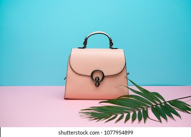 Stylish light brown leather female bag on the pink surface on the cyan background in the studio. There is a green branch next to it. Closeup. Horizontal.