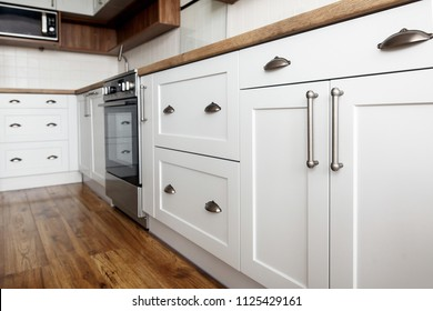 Stylish light gray handles on cabinets close-up, kitchen interior with modern furniture and stainless steel appliances. kitchen design in scandinavian style