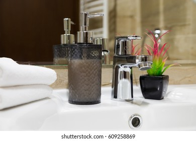 Stylish liquid soap pump and potted flowering plant on a white hand basin with clean towels in a hotel or home, close up view