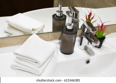 Stylish liquid soap pump and potted flowering plant on a white hand basin with clean towels in a hotel or home, high angle close up view
