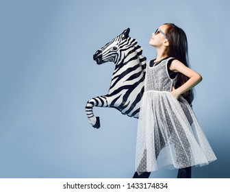 Stylish little asian girl kid in high fashion clothes and sunglasses posing in profile with zebra metallic balloon on menthol blue background with free text copy space