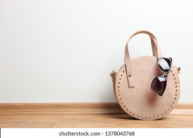 Stylish little beige round female handbag and sunglasses on wooden floor on neutral background. Concept accessory. Copy space.
