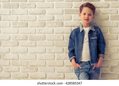 Stylish little boy in jeans clothes is looking at camera and smiling, standing with hands in pockets against white brick wall