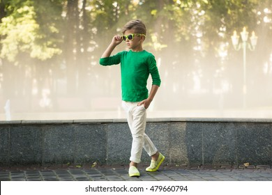 Stylish little boy in sunglasses and fashionable clothes . Children's fashion