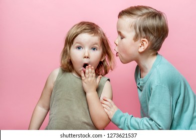 Stylish little boy whispering to surprised girl in her ear. A couple of children whispering secret against pink background. Friends.