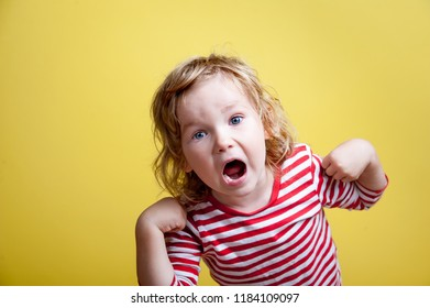 Stylish little child girl shouting loud. Excited child looking in camera isolated on yellow background. Portrait of shocked and surprised little girl. Back to school.