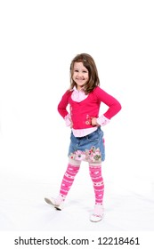 Stylish little girl in pink striped tights and a patterned short denim skirt.