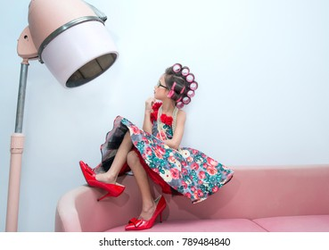 Stylish little girl portrait with hair curlers and red sunglasses. Kid's fashion