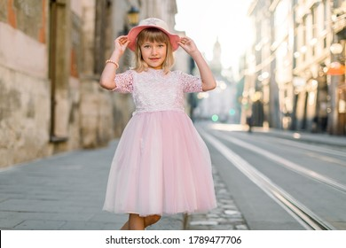 Stylish little girl wearing pink dress and hat, posing outdoors in the old European city, in sunny summer morning. Kid fashion concept
