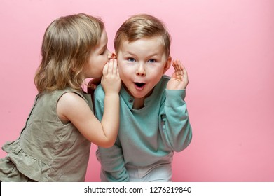 Stylish little girl whispering to shocked and surprised school boy in ear. A couple of children whispering secret against pink background. Friends
