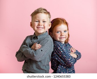Stylish little school boy and cute girl with yellow skateboard and wearing fashion clothes on a colorful pink background. Happy smiling children. Brother and sister together