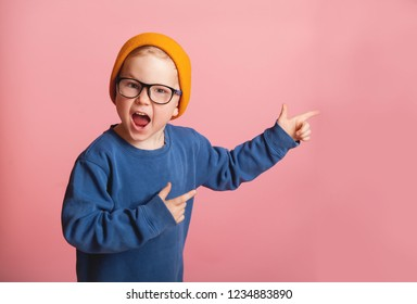 Stylish little school boy shouting. Toddler kid wearing fashion yellow hat and glasses on a colorful pink background. Happy smiling child with pointing fingers.