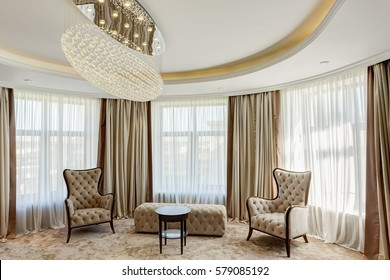 Stylish living room with big crystal chandelier in center of ceiling. Interior in beige and white colors. Room with cozy two armchairs and rounded wooden table between.