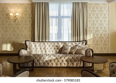 Stylish living room with big windows in beige and brown colors. Classic interior of big room with beige sofa, two rounded wooden table.