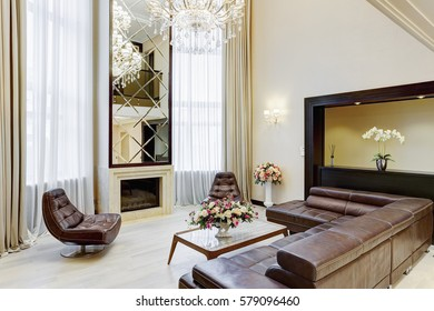 Stylish living room in brown, white and beige colors with fireplace and big mirror over, leather sofa and armchairs around. Big windows and glasses table with flowers on table.