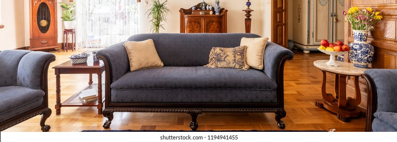 A stylish living room interior with antique furniture. Classic sofa on wooden floor. Panorama. Real photo.