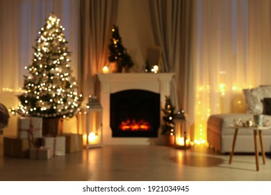 Stylish living room interior with Christmas tree near beautiful fireplace, blurred view
